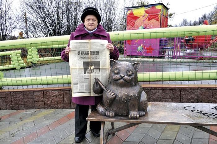 Хозяйка легендарного кота с газетой, где написана статья о его счастливом возвращении. / Фото: www.kpcdn.net